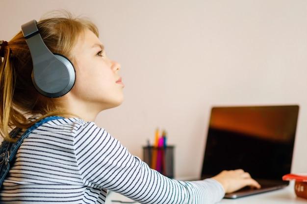 Portret van een meisje dat online met hoofdtelefoons en laptop leert die nota's in een notitieboekjezitting bij haar bureau neemt dat thuis huiswerk doet