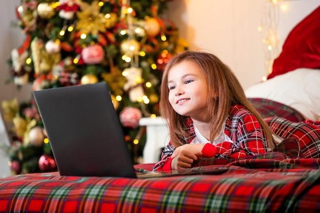 Portret van een meisje dat op een bed van een kerstboom ligt en een laptopmonitor onderzoekt.