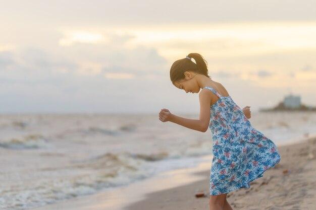 Portret van een meisje dat op het strand staat, een aziatisch kind dat ontspant in de zomeravondlucht buiten