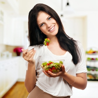 Portret van een meisje dat positief kijkt en een schreeuwt met salade houdt