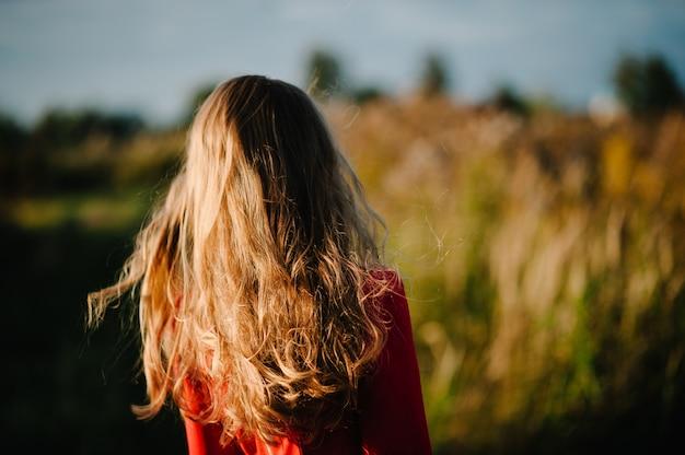 Portret van een meisje dat zich in de herfst in een rode jurk tegen het veld op de aard bevindt. bovenste helft. detailopname. uitzicht vanaf de achterkant.