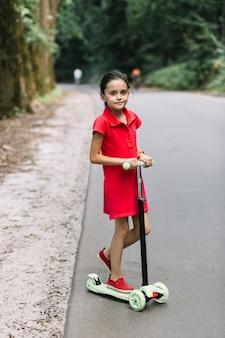 Portret van een meisje dat zich over autopedden op weg bevindt