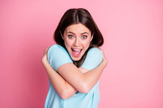 Portret van een meisje dat zichzelf knuffelt, geniet van geïsoleerd over pastelkleurige achtergrond