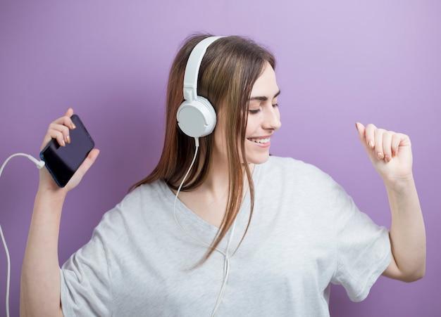Portret van een meisje die aan muziek op hoofdtelefoons luisteren en een dansend meisje.