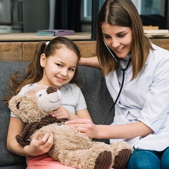 Portret van een meisje die de teddybeer met stethoscoop onderzoeken