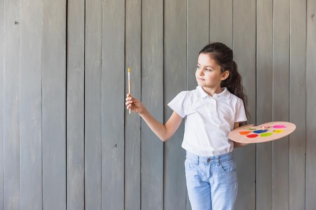 Portret van een meisje die houten palet houden die ter beschikking verfborstel in hand bekijken