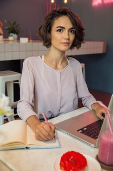 Portret van een meisje die op laptop typen en nota's schrijven