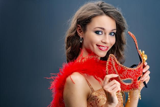 Portret van een meisje die speels de camera in een rode boa rond haar hals bekijken