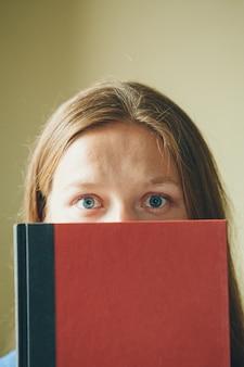 Portret van een meisje: een vrouw kijkt uit van achter een boek. de student gebruikt literatuur als schrijfruimte. ogen dicht omhoog