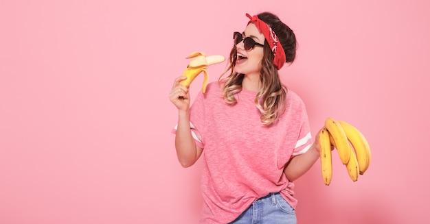 Portret van een meisje en bananen dat op roze muur wordt geïsoleerd