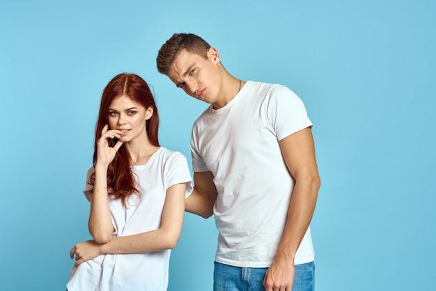 Portret van een meisje en een jongen op een blauwe muur in witte t-shirts en spijkerbroeken