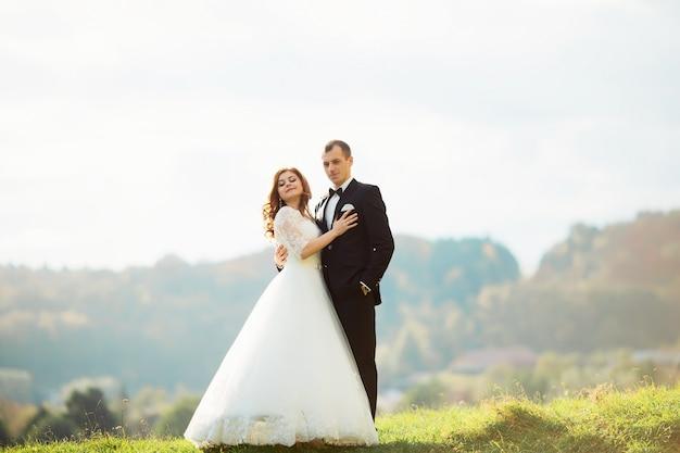 Portret van een meisje en koppels op zoek naar een trouwjurk, een roze jurk vliegen met een bloemenkrans op haar hoofd op een tsvetuschago-tuin op de achtergrond en de blauwe hemel, en ze knuffelen en poseren