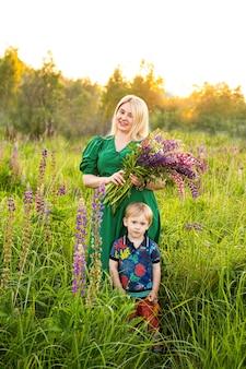 Portret van een meisje en zoon in een bloeiend veld in de zon bij zonsondergang