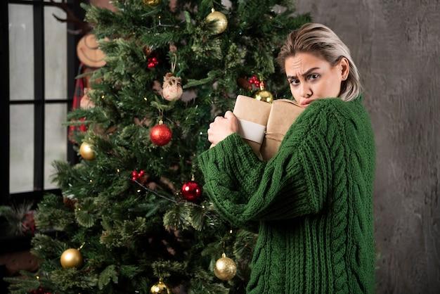 Portret van een meisje gekleed in een groene trui met stapel geschenkdozen en camera te kijken