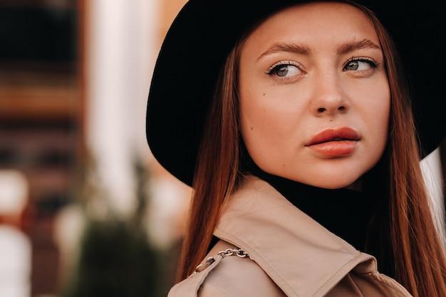Portret van een meisje in een beige jas en zwarte hoed op een stadsstraat. street fashion voor dames. herfstkleding. stedelijke stijl.