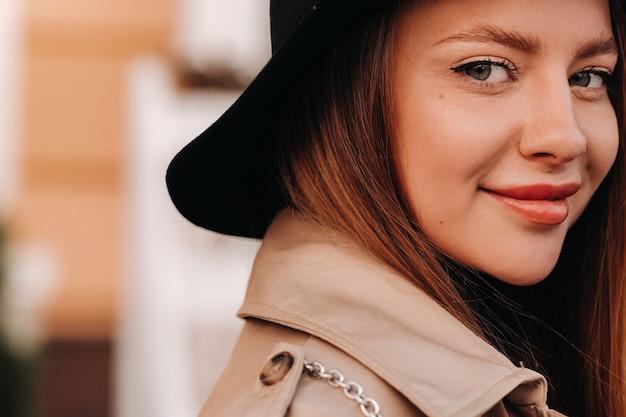 Portret van een meisje in een beige jas en zwarte hoed op een stadsstraat.