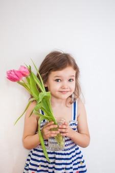 Portret van een meisje in een blauwe gestreepte jurk, een klein meisje poseren voor een portret