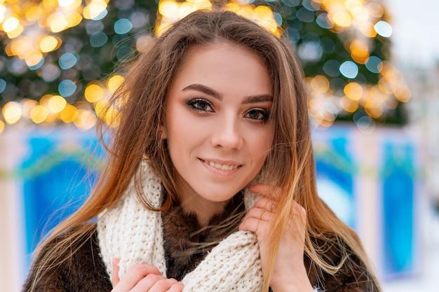 Portret van een meisje in een bontjas op de achtergrond van een kerstboom.