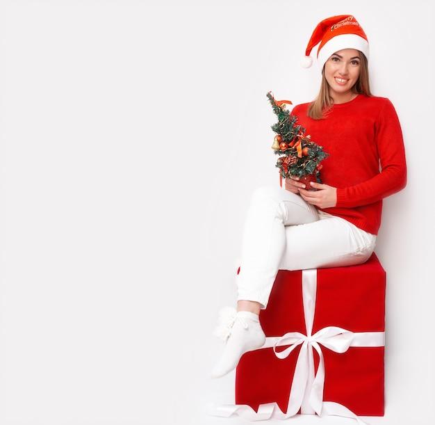 Portret van een meisje in een kerstmuts en rode trui met een kerstboom zittend op een large