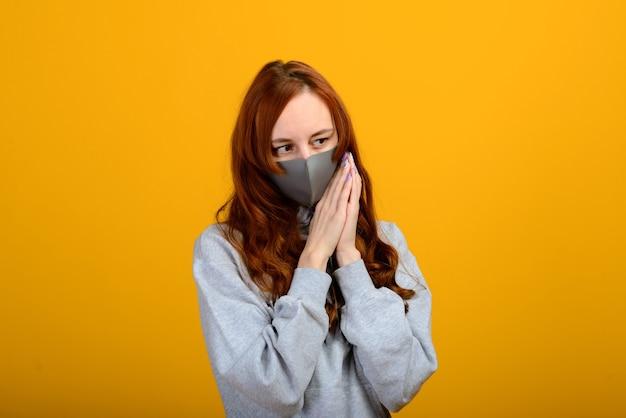 Portret van een meisje in een masker, dat een rubberen handschoen aantrekt. gele achtergrond.