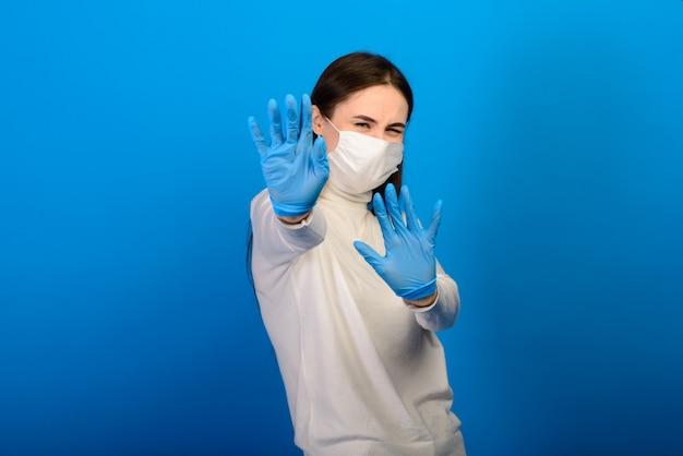 Portret van een meisje in een medisch masker, dat op een rubberen handschoen zet.