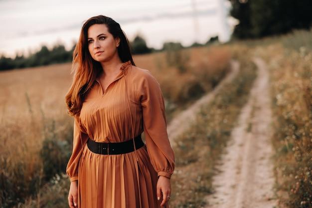 Portret van een meisje in een oranje lange jurk met lang haar in de natuur in de avond.