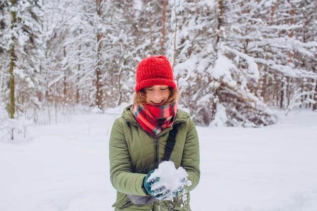 Portret van een meisje in een rode hoed en sjaal in het winterbos