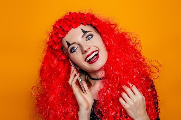 Portret van een meisje in een rode pruik en kostuum voor halloween met een telefoon in haar handen.