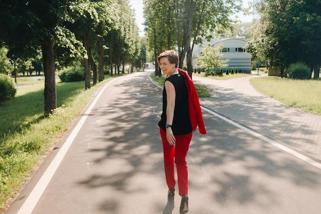 Portret van een meisje in een rood pak dat in het steegje van het park staat.