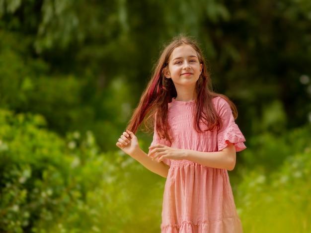 Portret van een meisje in een roze jurk in het park. buitenshuis. lifestyle en geluk concept.