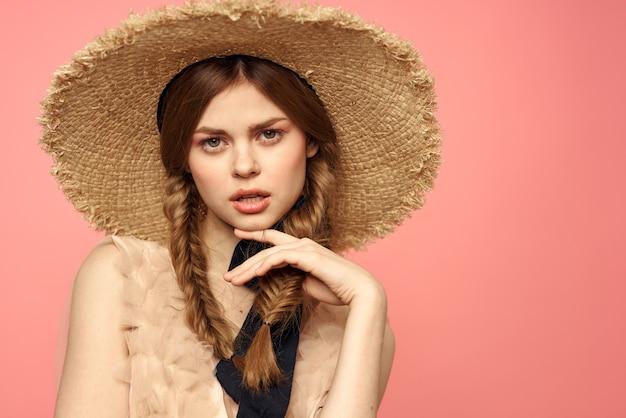 Portret van een meisje in een strooien hoed op een roze emoties close-up mooi gezicht model pigtails.