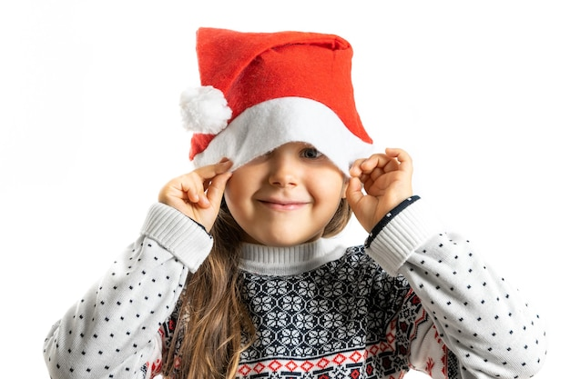 Portret van een meisje in een witte gebreide kersttrui met een rendier dat een half gezicht verbergt in de kerstman ha...