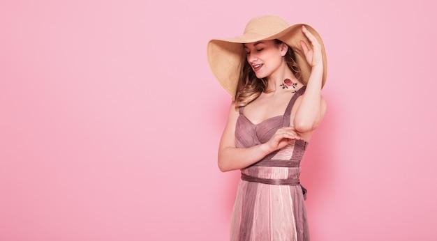 Portret van een meisje in een zomer hoed en jurk op een roze muur
