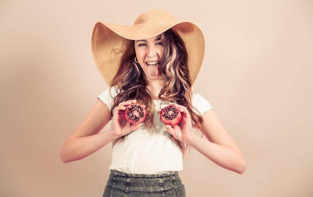 Portret van een meisje in een zomer hoed met fruit op een gekleurde achtergrond
