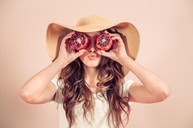 Portret van een meisje in een zomer hoed met fruit op een gekleurde muur