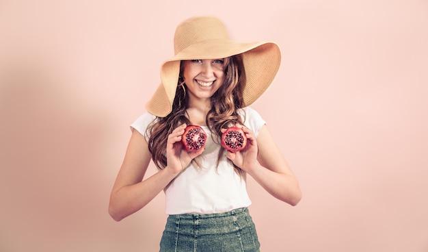Portret van een meisje in een zomerhoed met fruit op een gekleurde achtergrond