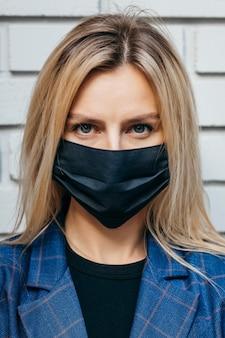 Portret van een meisje in een zwart medisch masker close-up