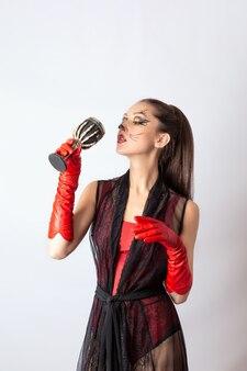 Portret van een meisje in een zwarte jurk en rode handschoenen met een wijnbeker in haar hand