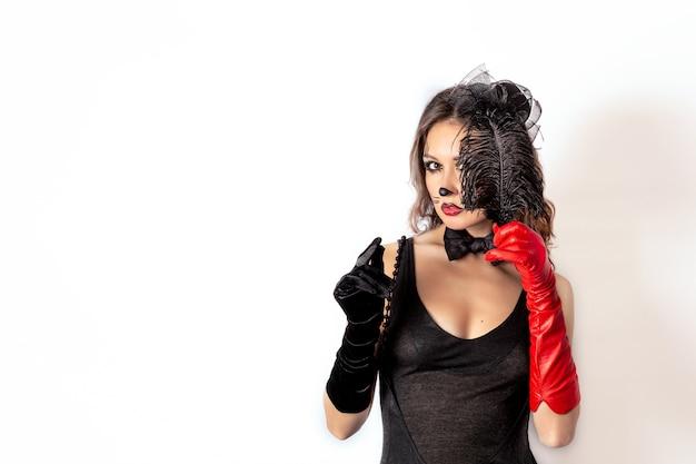 Portret van een meisje in een zwarte jurk en zwarte en rode handschoenen met een hoed op haar hoofd