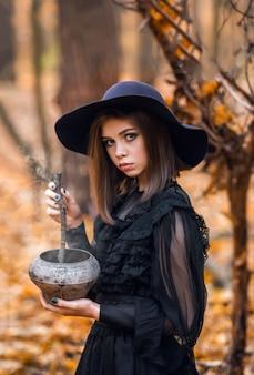 Portret van een meisje in een zwarte jurk in een herfstbos. een jonge heks.