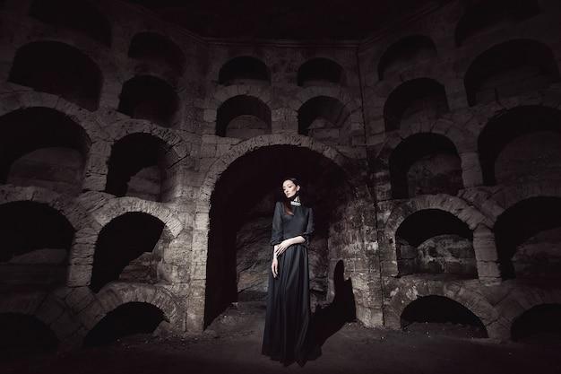 Portret van een meisje in een zwarte jurk met een witte kraag die zich in een stenen opening bevindt