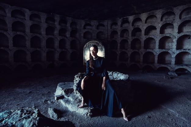 Portret van een meisje in een zwarte jurk met een witte kraag, zittend op een stenen put in een stenen opening