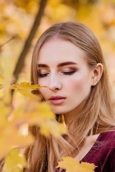 Portret van een meisje in gele herfstbladeren