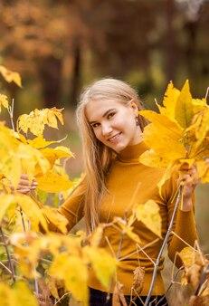 Portret van een meisje in het herfstbos. mooie vrouw in gele bladeren.