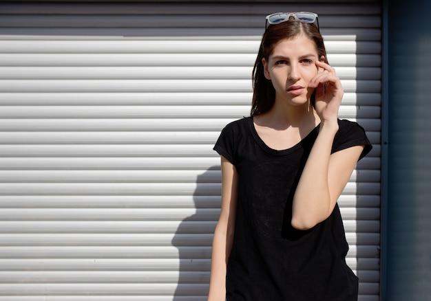 Portret van een meisje in rockzwarte stijl dat buiten in de stad staat tegen de zilveren metalen stadsmuur