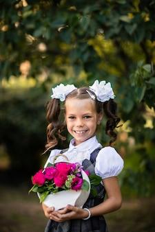 Portret van een meisje in schooluniform met witte bogen