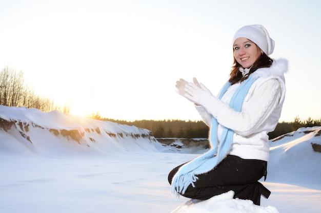 Portret van een meisje in witte muts en handschoenen, glimlachend en haar handpalmen bij elkaar te houden, buiten bij zonnig weer