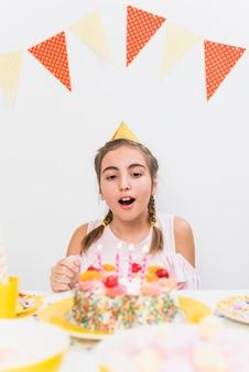 Portret van een meisje klaar om verjaardagskaars te blazen