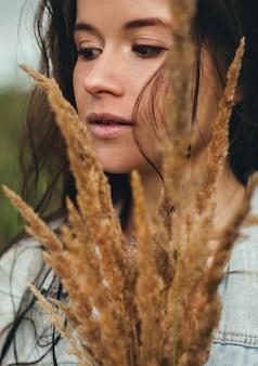 Portret van een meisje met een boeket tarwe