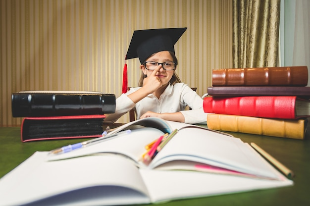Portret van een meisje met een bril en een afstudeerpet die aan het bureau poseert